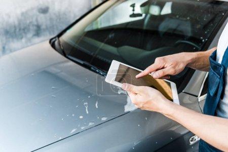 Photo pour Mise au point sélective de nettoyeur de voiture pointant avec le doigt à la tablette numérique avec écran blanc - image libre de droit