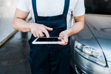 Photo pour Foyer sélectif de l'homme pointant avec le doigt à la tablette numérique près de la voiture - image libre de droit