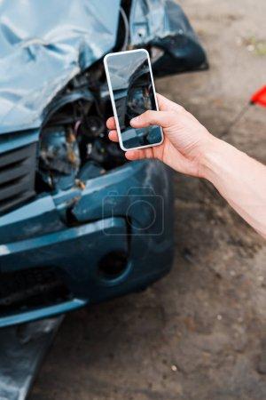 Photo pour Vue recadrée de l'homme retenant le smartphone avec l'écran blanc près de la voiture endommagée - image libre de droit
