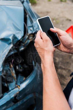 Photo pour Vue recadrée de l'homme retenant le smartphone avec l'écran blanc près de la voiture écrasée - image libre de droit