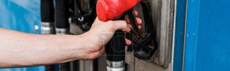 Photo pour Tir panoramique de l'homme retenant la pompe à essence rouge sur la station-service - image libre de droit
