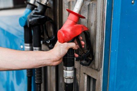 Photo pour Foyer sélectif de l'homme retenant la pompe à essence rouge sur la station-service - image libre de droit