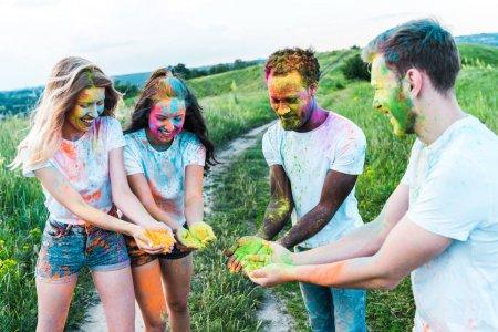Foto de Felices amigos multiculturales sosteniendo coloridas pinturas holi en las manos - Imagen libre de derechos