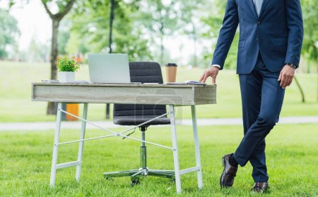 Foto de Cropped view of young businessman standing with crossed legs near table in park - Imagen libre de derechos