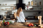 young woman in white shirt standing in kitchen and looking away