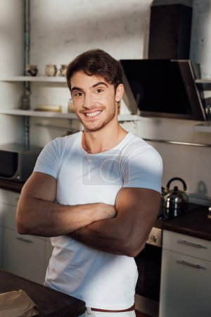 Photo for Muscular man in white t-shirt standing with crossed arms and smiling in kitchen - Royalty Free Image