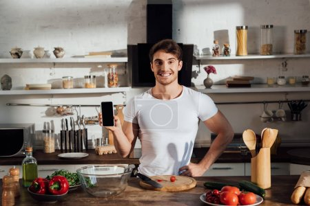 Photo for Front view of smiling muscular man in white t-shirt showing smartphone with blank screen while cooking in kitchen - Royalty Free Image
