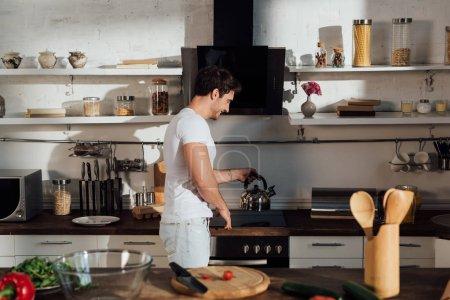 Photo pour Homme musculaire de sourire dans le t-shirt blanc mettant la bouilloire sur le four dans la cuisine - image libre de droit