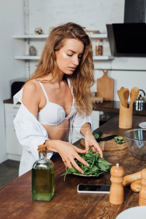 Photo for Sexy woman in white bra cooking salad in kitchen - Royalty Free Image