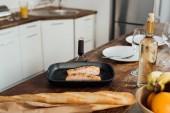 """Постер, картина, фотообои """"рыба в сковороде, фрукты, багеты и вино на столе на кухне"""""""