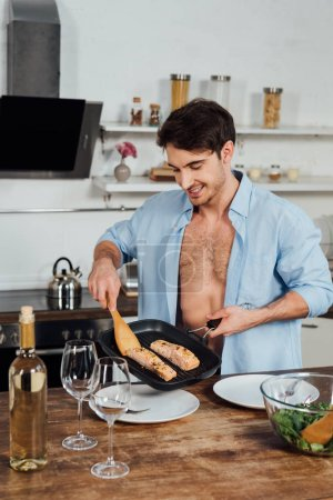 Photo for Sexy smiling man holding frying pan with fish in kitchen - Royalty Free Image