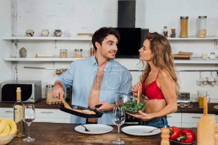 Photo for Sexy couple cooking together and smiling in kitchen - Royalty Free Image