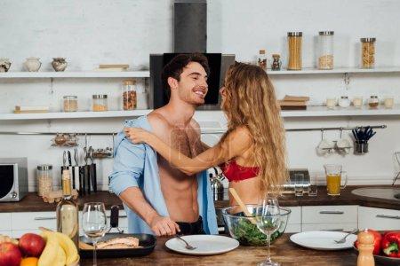 Photo pour Fille sexy déshabiller petit ami près de la table servie dans la cuisine - image libre de droit