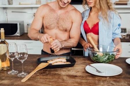 Photo for Cropped view of sexy couple cooking together in kitchen - Royalty Free Image