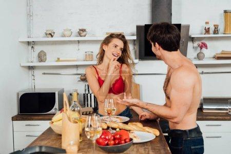Photo pour Sourire couple sexy debout près de la table avec de la nourriture et en regardant les uns les autres - image libre de droit