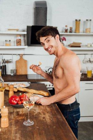 Photo pour Homme musclé souriant debout près de la table avec de la nourriture et manger dans la cuisine - image libre de droit