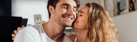 Photo for Panoramic shot of charming girl kissing boyfriend in cheek in kitchen - Royalty Free Image