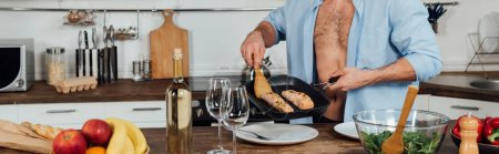 Photo for Panoramic shot of man holding frying pan and cooking fish in kitchen - Royalty Free Image