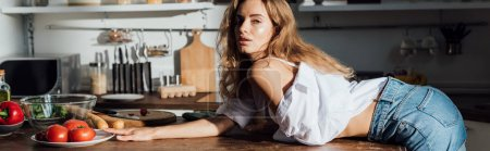 Photo for Panoramic shot of sexy girl lying on table and looking at camera in kitchen - Royalty Free Image
