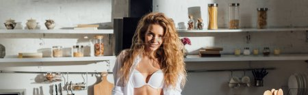 Photo for Panoramic shot of smiling sexy girl in white bra looking at camera in kitchen - Royalty Free Image