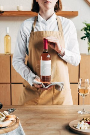 partial view of sommelier in apron holding bottle of wine