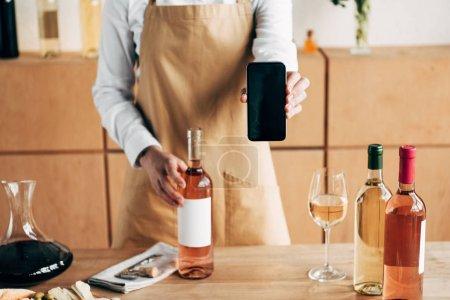 Photo pour Vue partielle du sommelier dans le tablier restant près de la table avec des bouteilles de vin et affichant le smartphone avec l'écran blanc - image libre de droit