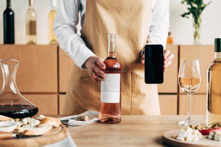 Photo for Partial view of sommelier in apron standing near table with bottles of wine and showing smartphone with blank screen - Royalty Free Image