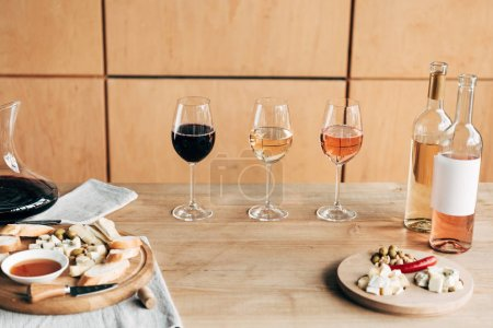 wine glasses, bottles of wine and food on wooden table