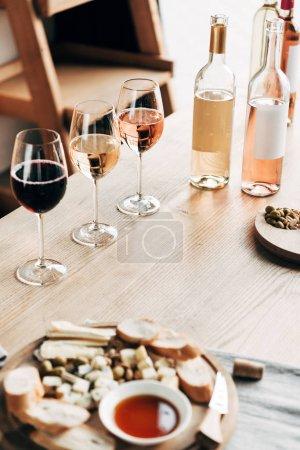 Photo pour Verres à vin, bouteilles de vin et nourriture sur table en bois - image libre de droit