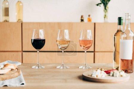 Photo pour Verres à vin, bouteilles et nourriture sur table en bois - image libre de droit
