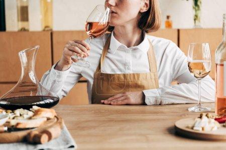 Photo pour Vue partielle du sommelier dans le tablier s'asseyant à la table et goûtant le vin - image libre de droit