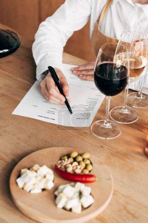 Photo pour Vue recadrée du sommelier dans le tablier assis à table et écrit dans le document de dégustation de vin - image libre de droit