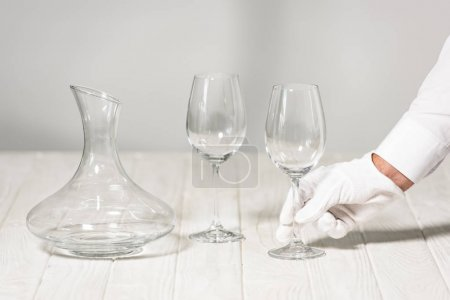 Photo for Partial view of waiter holding empty wine glass in restaurant - Royalty Free Image