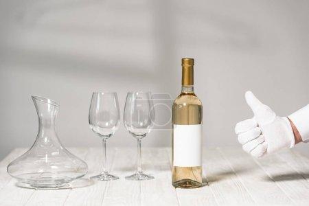 Photo pour Vue partielle du serveur dans le gant blanc affichant le pouce vers le haut près de la table avec la bouteille de vin, les glaces de vin et la cruche - image libre de droit