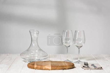 Photo pour Cruche, verres à vin, couverts et planche à découper sur la surface en bois dans le restaurant - image libre de droit