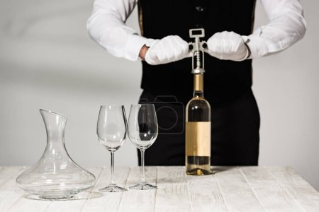 Photo for Partial view of waiter in white gloves opening bottle of wine with corkscrew - Royalty Free Image