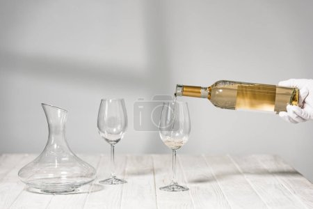 Photo for Cropped view of water in white glove holding bottle of wine near wine glasses on wooden table - Royalty Free Image