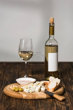 Photo for Bottle of wine, wine glass, cheese, olives, sauce and bread on wooden surface - Royalty Free Image