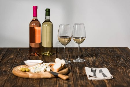 Photo for Bottles of wine, wine glasses, cutlery, cheese, olives, sauce and bread on wooden surface - Royalty Free Image