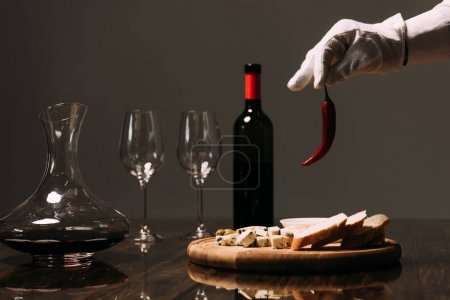 Photo for Cropped view of waiter in white glove holding pepper near table with food and wine - Royalty Free Image