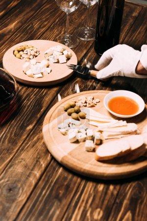 Photo pour Vue recadrée de serveur dans le gant blanc près de la table avec la nourriture et le vin - image libre de droit