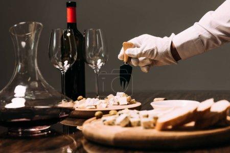 Photo pour Vue recadrée de serveur dans la fourchette blanche de fixation de fromage de gant près de la table avec la nourriture et le vin - image libre de droit
