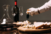 cropped view of waiter in white glove holding cheese fork near table with food and wine