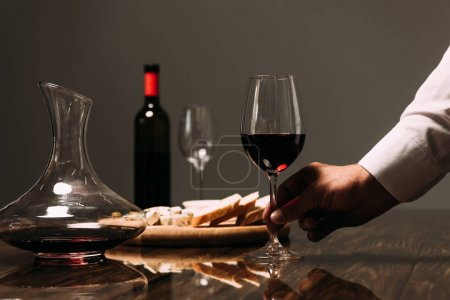 Photo for Cropped view of man holding wine glass at table in restaurant - Royalty Free Image