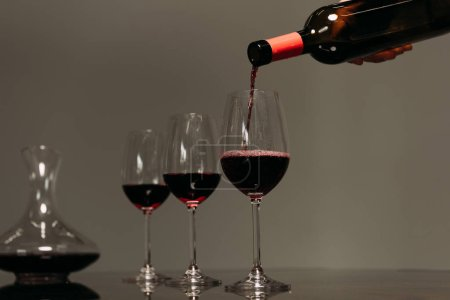 Photo for Partial view of man pouring wine in wine glasses in restaurant - Royalty Free Image
