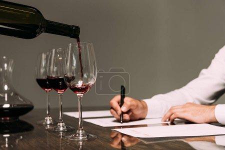 Photo pour Vue partielle du sommelier écrivant à table avec des verres à vin - image libre de droit