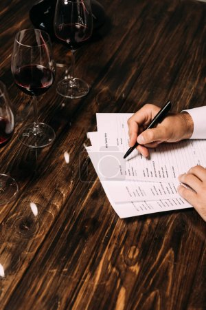 Photo for Partial view of sommelier writing at table with wine glasses - Royalty Free Image