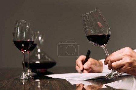 Photo pour Vue partielle du sommelier écrivant à table et tenant un verre à vin - image libre de droit
