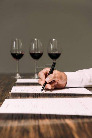 Photo pour Vue recadrée de sommelier écrivant dans des documents à table avec des verres à vin - image libre de droit