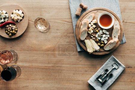 Photo pour Vue du haut des verres à vin, de la nourriture, du tire-bouchon et des bouchons sur la surface en bois - image libre de droit